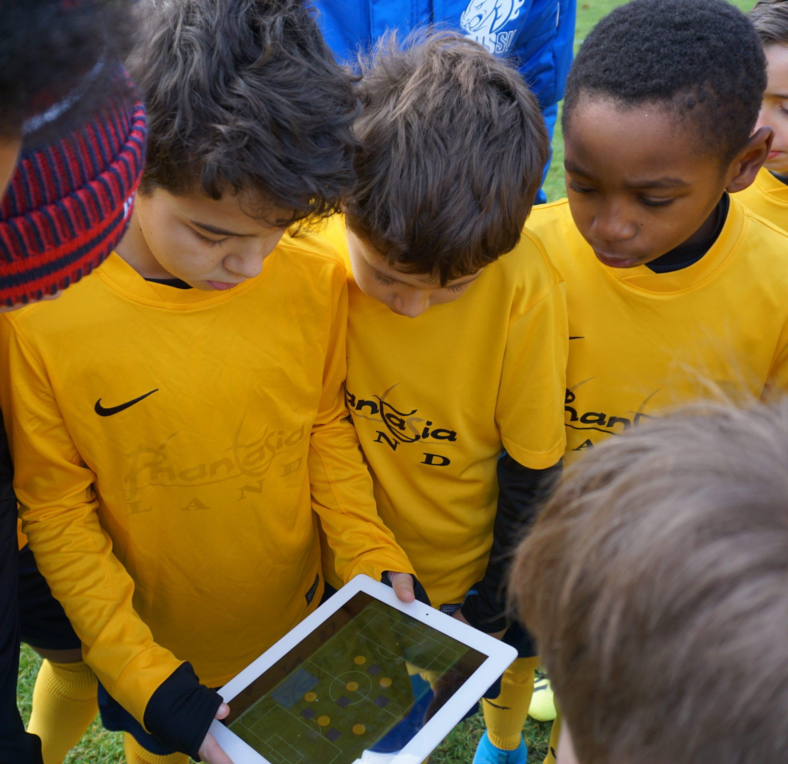Die Spieler betrachten aufmerksam die Taktik-Anweisungen auf dem Tablet