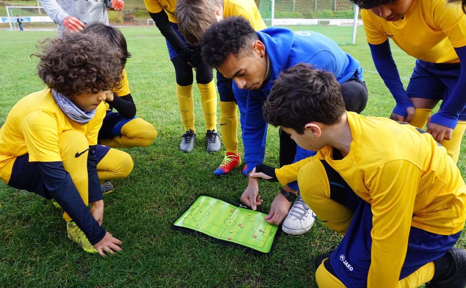 Trainer bespricht Anweisungen mit Kindern auf Taktiktafel
